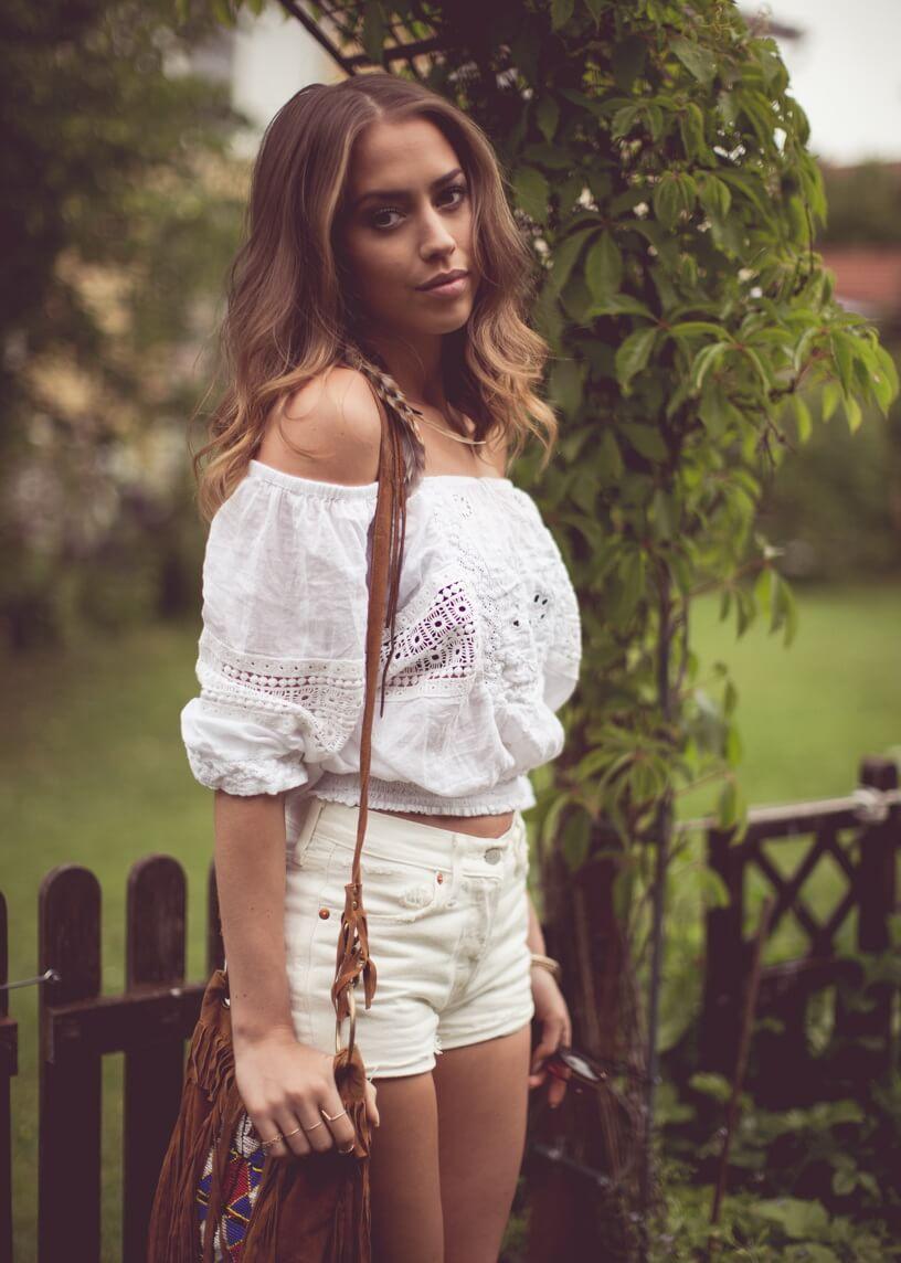 белые джинсовые шорты с белой рубашкой на плечах