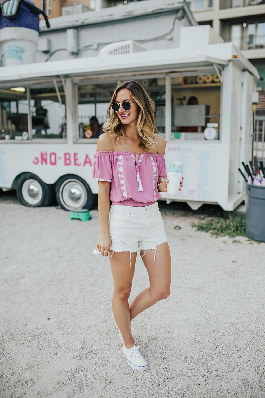 белые джинсовые шорты с розовым топом на плечах